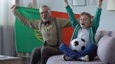vlag portugal : Grandpa and grandson watching football, waving Portuguese flag, happy for win