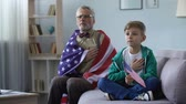 electing : Patriotic old man holding American flag, singing national anthem with grandson