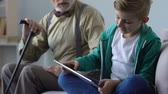 rés : Grandfather lecturing small boy playing tablet game, critizing child behavior