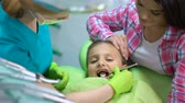 pravidelný : Little girl on regular dental examination, mother holding daughter, calming Dostupné videozáznamy