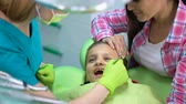 qualified : Child afraid of dental examination, doctor and parent calming little girl