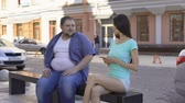 junggeselle : Fit beautiful woman ignoring fat man sitting on bench, sad unconfident bachelor Stock Footage