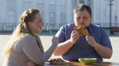 doba jídla : Young female eating vegetable salad, man chewing fried chicken, diet choice