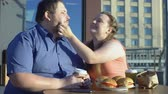 tembellik : Smiling woman treating boyfriend french fries, fat couple date, unhealthy food