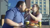 tembellik : Oversize couple sharing burgers during romantic date outdoors, calories and diet Stok Video
