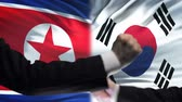 oposicion : North Korea vs South Korea confrontation, neighbors fists on flag background