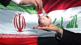umsetzung : Iran investment in Iraq, hand putting money in piggybank on flag background