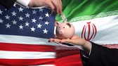 globalizace : US investment in Iran, hand putting money in piggybank on flag background