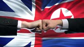 enemy : Great Britain vs North Korea conflict, fists on flag background.