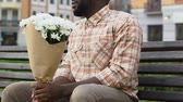 end up : Upset man sitting on bench, holding flowers, waiting in vain for girlfriend Stock Footage