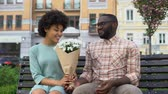 blinden : Young man giving white flower bouquet to woman sitting bench, first awkward date Stockvideo
