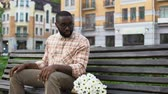 blinden : Nervous young man waiting for girl, sitting park bench with flowers, blind date
