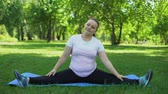 perder : Obese girl doing splits, fitness exercises outdoors, way to healthy lifestyle