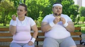 здравоохранение : Fat girl eating apple, obese man having burger, individual choice of proper food Стоковые видеозаписи
