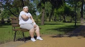 ischemic : Fat man having heart attack when jogging in park, obesity causes health problems