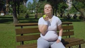 здравоохранение : Obese girl eating apple after jogging, healthy diet, proper lunch with vitamins