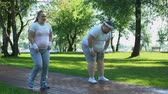 здравоохранение : Fat couple jogging in park, support each other, mutual desire to lose weight