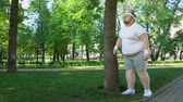 трудный : Fat man tired after running in park, leaning on tree, tiresome workouts outdoors Стоковые видеозаписи