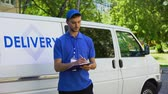 postacı : Parcel delivery worker filling report and smiling, part-time job, occupation