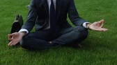 otimismo : Office worker sits in lotus pose on lawn, distracts from problems, meditation