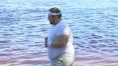 buclatý : Chubby male and female running along waterfront, trying to lose weight. Dostupné videozáznamy