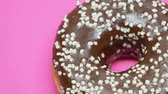 elhízottság : Spinning chocolate donut on pink background, temptation during diet. Stock mozgókép