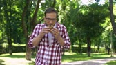 vřed : Guy chewing fast food burger in park feeling nausea, food poisoning symptom