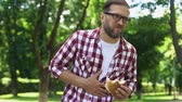 vřed : Man with burger in hand feeling nausea, junk food poisoning, body intoxication Dostupné videozáznamy