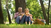 pensão : Cheerful old couple resting on grass and eating burgers, romantic date in park