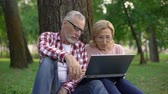 魅惑的な : Happy retired man and woman sitting on grass and watching movie on laptop pc