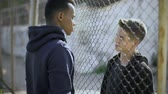 begrip : Two boys of different nationalities talking, rich and poor separated by fence