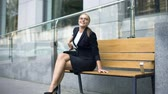 supporting : Happy businesswoman sits on bench, pleased with successful working day, rest Stock Footage
