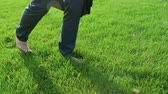 kolaylık : Barefoot business person walking on lawn in park, relaxation, unity with nature Stok Video