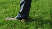 snadnost : Man in suit walks barefoot on lawn, office worker relaxing after work. Dostupné videozáznamy