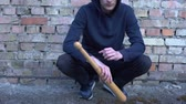 morcego : Young bandit sitting near brick wall holding bat, city hooligan high-crime area