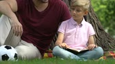 valores : Dad and kid reading book, father explaining difficult items to son, education