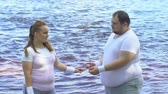 solitário : Break-up of overweight couple, obese female leaving boyfriend and walking away