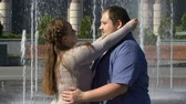 привязчивый : Beautiful plump woman tenderly hugging her obese boyfriend, outdoor date slow-mo