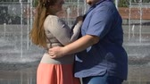 enjoying : Happy girlfriend hugging her overweight boyfriend, enjoying romantic date