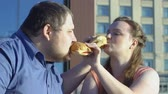 positività : Happy plus size couple treating each other fatty burgers on date.