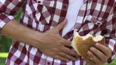 vřed : Hungry man eating unhealthy burger feeling stomach pain cholecystitis, gastritis