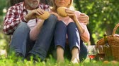 gastritis : Old couple eating burgers outdoors, junk food increase cholesterol.