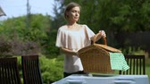 фреска : Female placing wicker picnic basket on table, outdoor picnic in country house