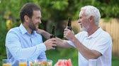 saúde : Senior and middle-aged men clinking beer bottles and talking, brewing traditions