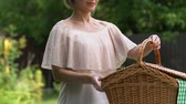 枝編み細工 : Young woman putting picnic basket on table and smiling at camera, housewife