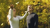 tossing up : Happy couple throwing up autumn leaves, sincere love and romantic feelings
