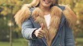 aprovar : Woman in autumn coat with fur showing thumbs up, advertising warm clothes