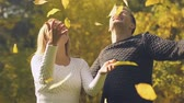 tossing up : Young couple throwing up autumn leaves, happy time together, romantic date