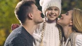 both : Parents kissing happy daughter on both cheeks, upbringing and love for child