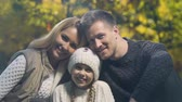 bem estar : Happy young family with beautiful daughter posing for camera in autumn forest